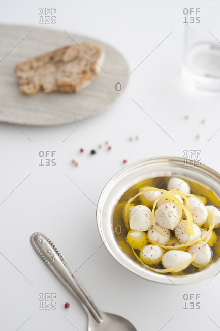 Fresh mozzarella balls in olive oil with cracked pepper and lemon rind on white background