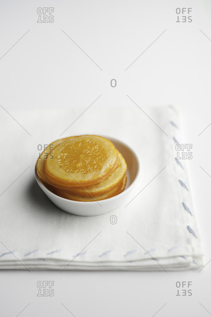 Stack of preserved orange slices in white bowl