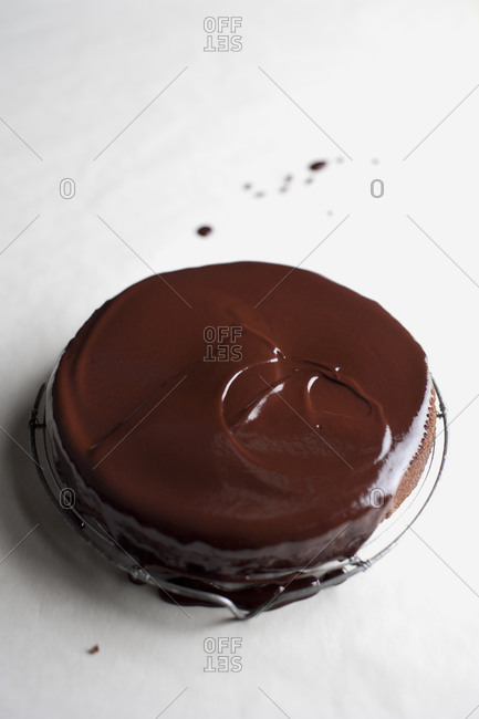Chocolate cake covered with ganache on white background