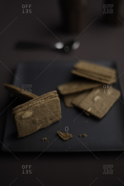 Thin almond cookies on square black plate