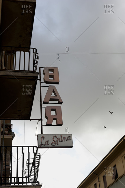 Bar sign hanging off building terrace under overcast skies