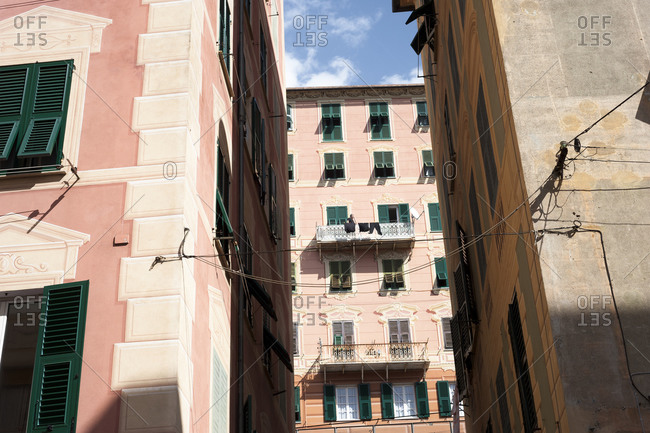 View of pink apartment building from alley between two pastel colored buildings in Italy