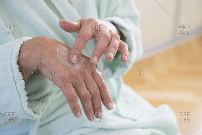 Senior woman applying moisturizer on her hand