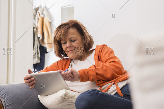 Relaxed senior woman working a digital tablet