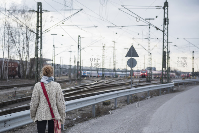 Rear view of a young woman curiously looking at train on railway track