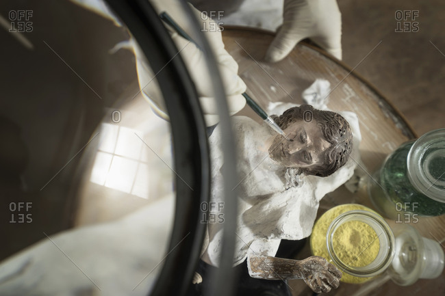 Sculptor works on a Jesus Christ statue at workshop