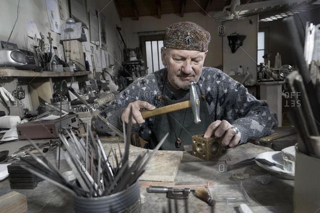 Senior male goldsmith metalworking at workshop