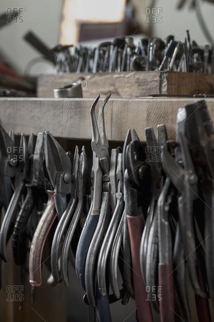 Various pliers hanging in workshop