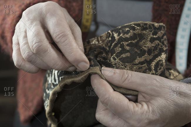 Senior female fashion designer stitching in workshop