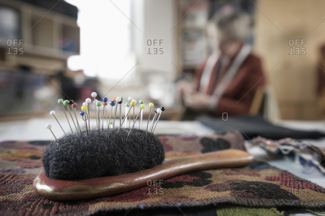 Close-up of pin cushion with senior female fashion designer working in workshop