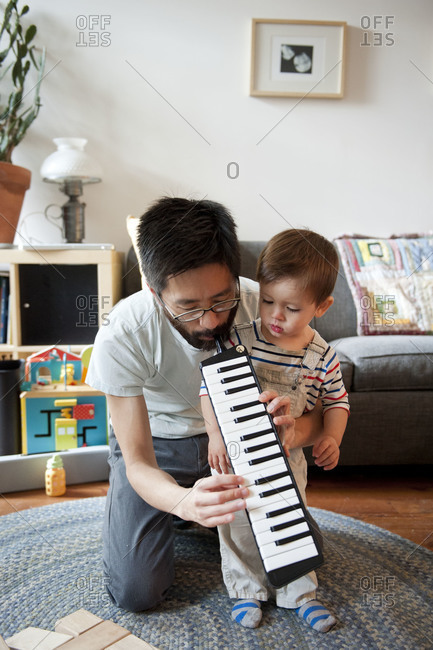 Father showing son how to play instrument