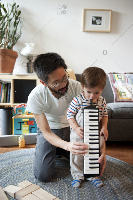 Father showing son how to play musical instrument