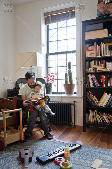 Father reads book to young son in his lap