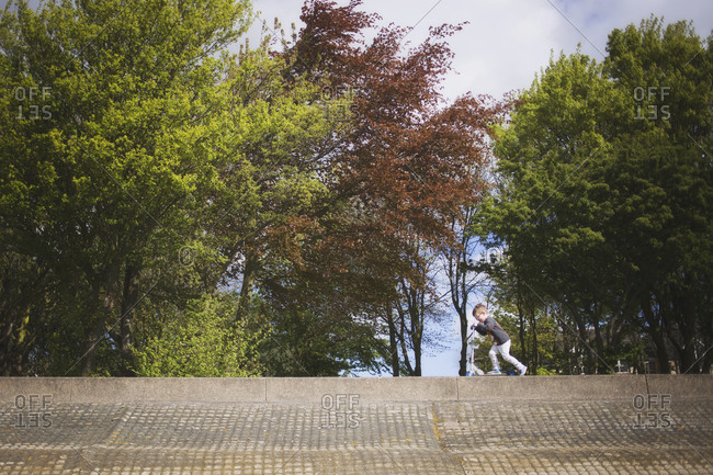Little boy riding a scooter along an embankment