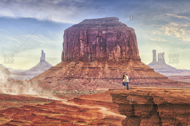 Couple kissing on a bluff in Monument Valley