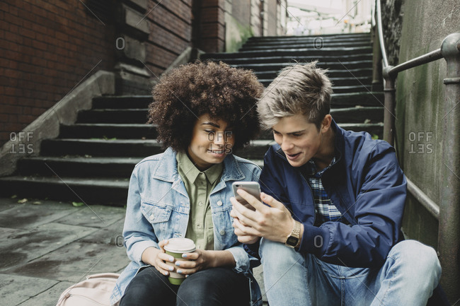 Young couple looking at a smartphone in Bristol, UK