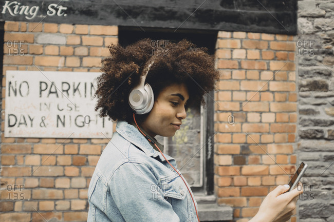 Young woman listening to music on a street