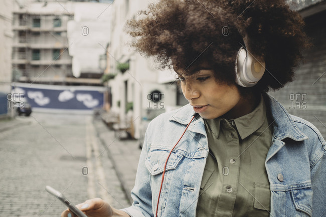 Young woman using a headphone on a street
