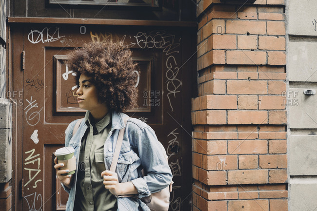 Young woman holding a cup of coffee on a street