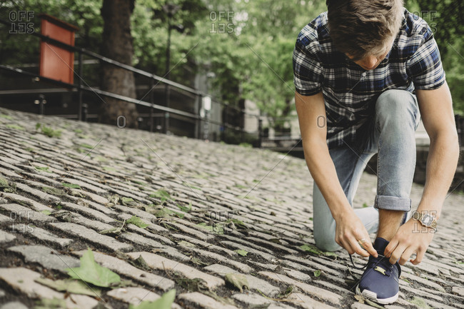 Young man tying his shoes on a street in Bristol, UK