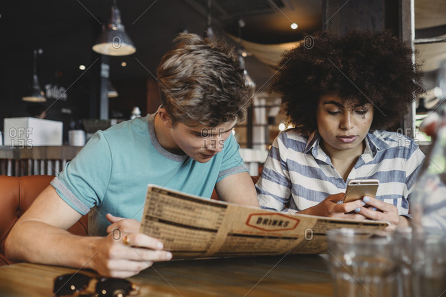 Man reading the menu while his girlfriend using a smartphone in a restaurant