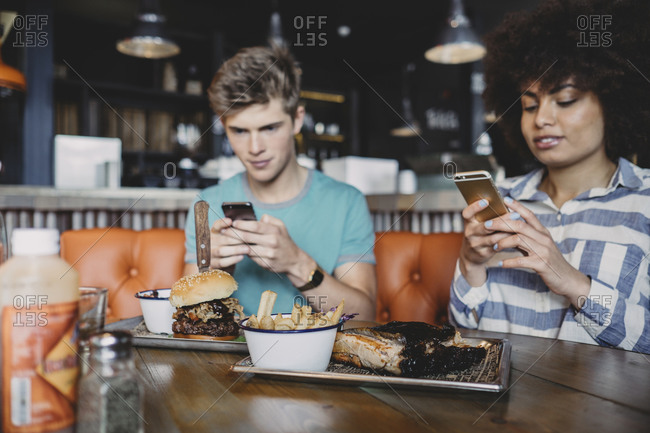 Couple using their smartphones in a restaurant