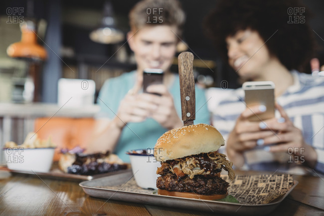 Couple taking a picture of a hamburger in a restaurant