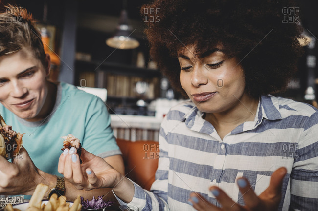 Couple eating a hamburger in a restaurant