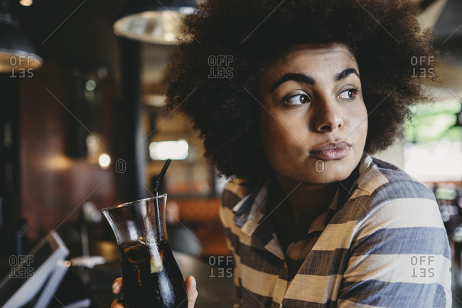 Woman drinking cola in a restaurant