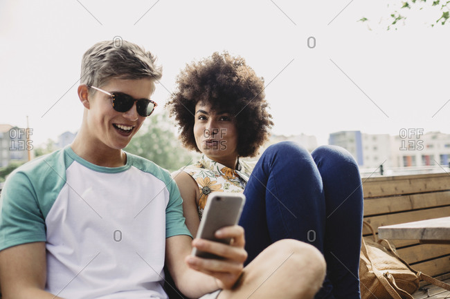 Young man using a smartphone next to her girlfriend on a bench