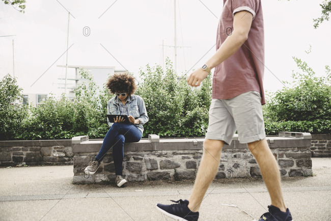 Young woman using a tablet while a man passing by on a street