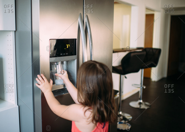Girl getting water from fridge dispenser