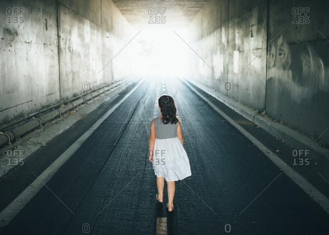 Girl walking down road under underpass