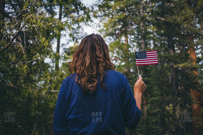 Woman in forest holding an American flag