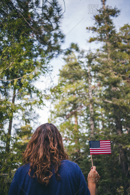 Woman in woods holding an American flag