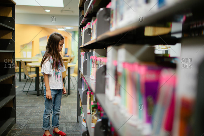 Young girl looking through library shelves