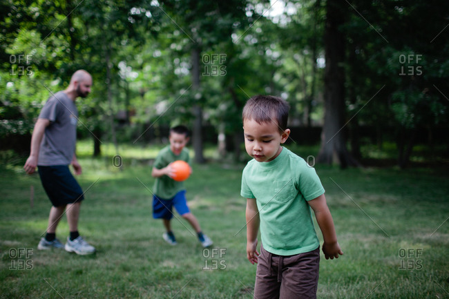 Dad playing ball with two boys