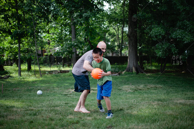 Dad and boy wrestling over ball in yard