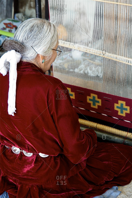 New Mexico, USA - August 7, 2008: Navajo elder demonstrates her weaving skills at a trading post in New Mexico