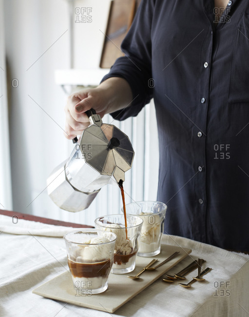 A woman pours coffee over vanilla ice cream