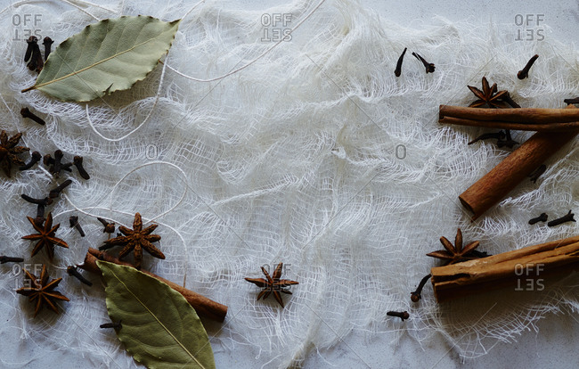 Star anise, bay leaves, cloves and cinnamon sticks on cheesecloth