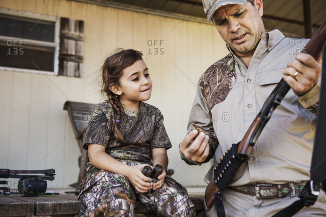 A dad shows his daughter how to load a rifle