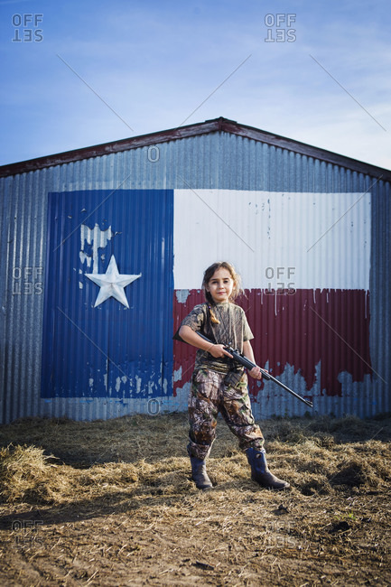 A girl with a rifle stands in front of a barn painted with a flag