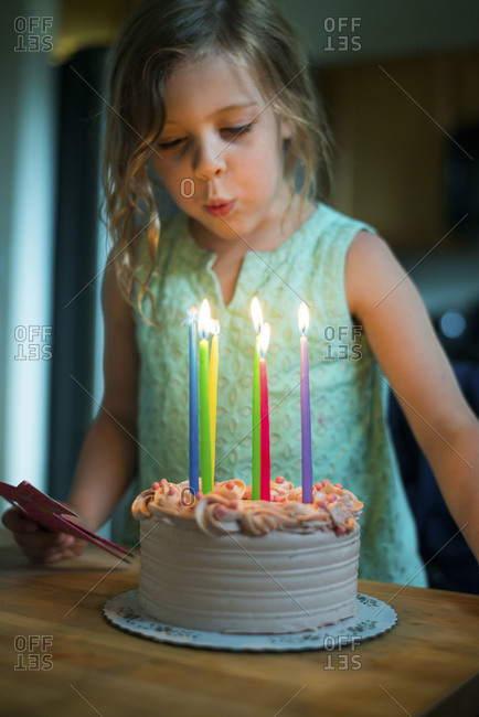 Girl standing over lit birthday candles