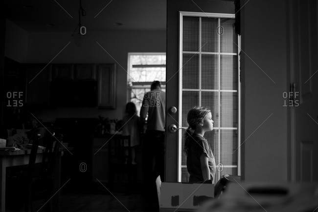 Girl in kitchen with family staring out door