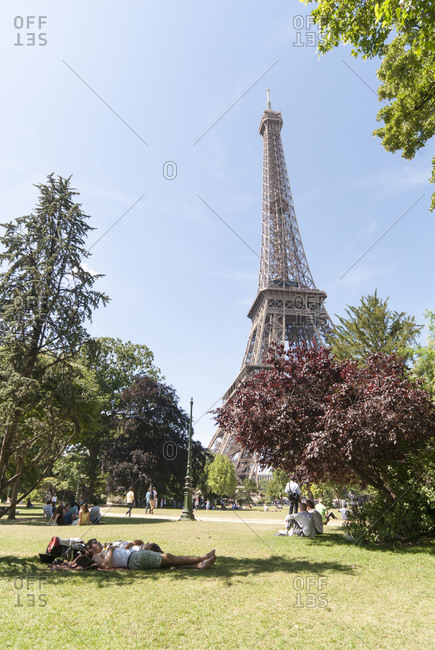 Paris, France - June 30, 2015: Eiffel Tower and sleeping tourists, Paris, France
