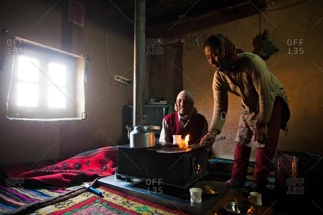 Himachal Pradesh, India - October 18, 2013: Couple around a stove in Spiti, Himachal Pradesh, India