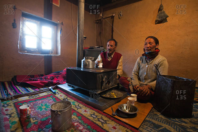Himachal Pradesh, India - October 19, 2013: Couple sitting next to a stove in Spiti, Himachal Pradesh, India