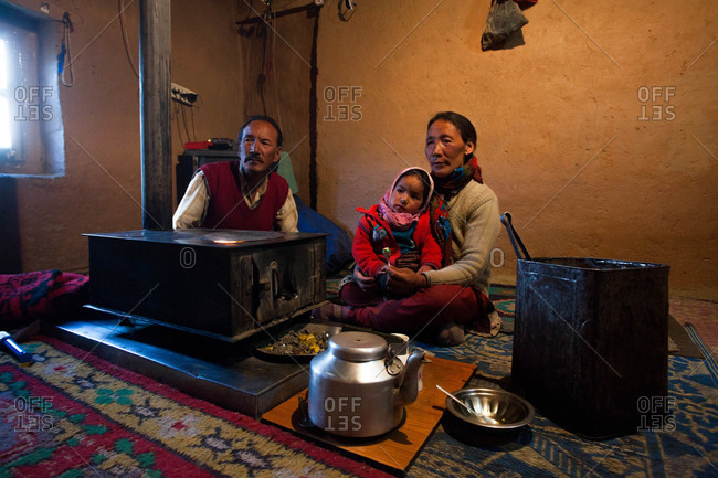 Himachal Pradesh, India - October 19, 2013: Family sitting next to a stove with in Spiti, Himachal Pradesh, India