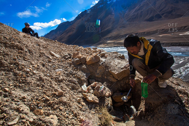 Himachal Pradesh, India - October 19, 2013: Man filling up a bottle with water on Langza road, Himachal Pradesh, India